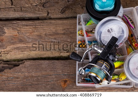 fishing tackles and fishing baits in box on vertical wooden board background. Design for outdoor sport business - templates, web, poster, card, advertisement. - stock photo