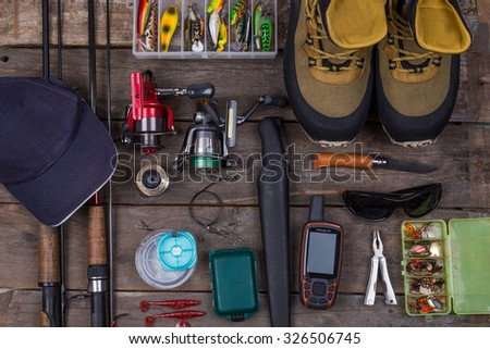 fishing tackles and fishing gear on tinber boards look on top - stock photo
