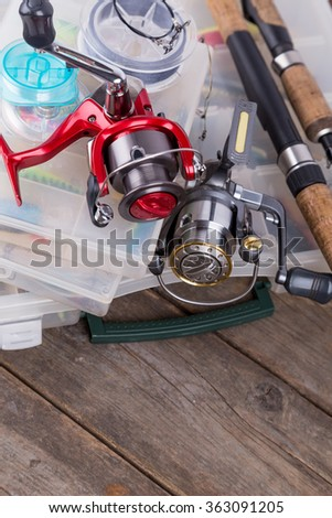 fishing tackles and lures, baits in storage boxes on background of wooden timbers