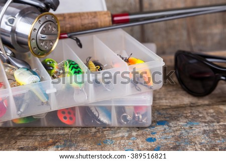 fishing tackles, lures and baits in boxes on wooden timbers background for outdoor active business