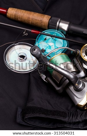 fishing tackles - rod, reel, line and lure on black jacket background - stock photo