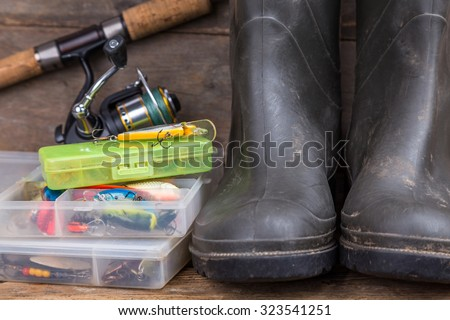 fishing tackles rod, reel, wobblers in boxes with rubber boots on timber board background. for design advertising or publication