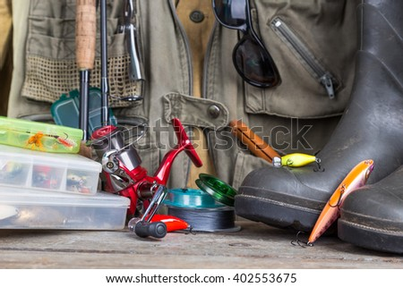 fishing tackles with fishing vest, boots and wooden boards. design background for outdoor  advertisement, flayer etc. - stock photo
