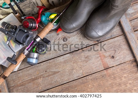fishing tackles with fishing vest, boots and wooden boards. design background for outdoor  advertisement, flayer etc.