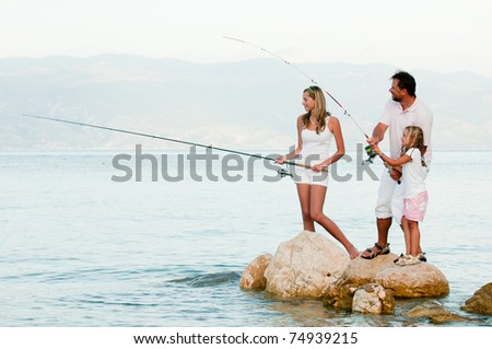 Fishing team - family fishing at the beach - stock photo