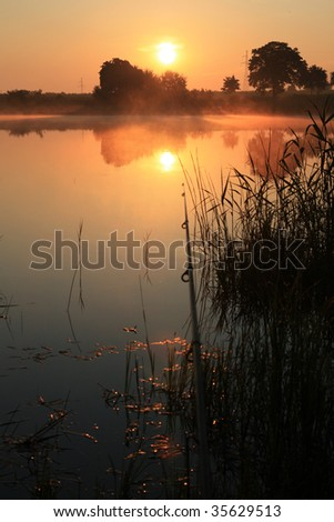 fishing time... rod and lake... sunerise - stock photo