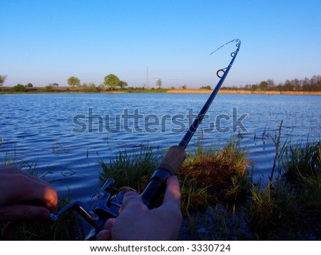 fishing time... sunset, rod and hand angler on the lake, catch of fish - stock photo