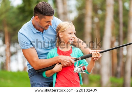 Fishing together is fun. Cheerful father and daughter fishing together and smiling - stock photo