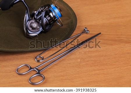 Fishing tools. Spinning reel and landing net - stock photo
