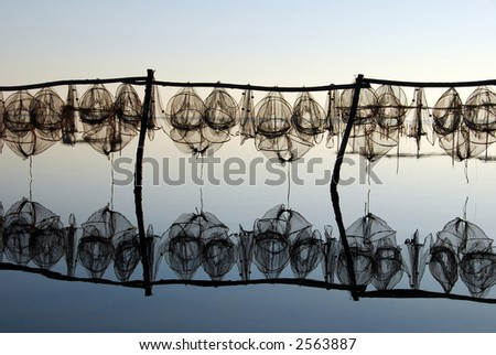 fishing traps and lovely reflection on dead calm sea