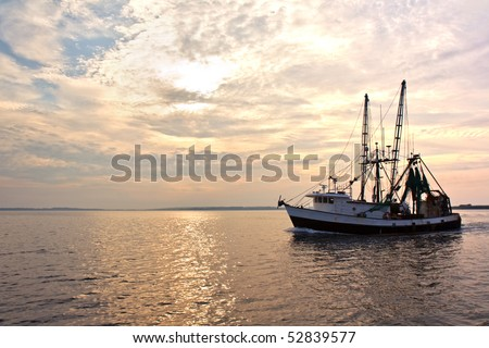 Fishing trawler on the water and dramatic clouds at sunrise