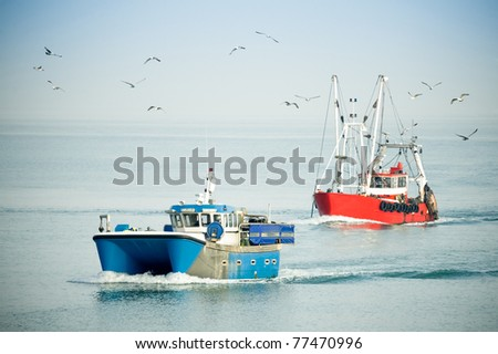 fishing trawlers returning to port on a hazy day surrounded by seagulls - stock photo