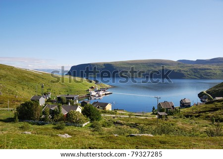 Fishing village is located on the side of blue fjord. Soroya is photographed in summer. There are wooden houses on the green grassy hills and a lot of blue water. - stock photo