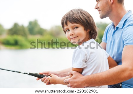 Fishing with my father. Cheerful father and son fishing together while little boy looking at camera and smiling - stock photo