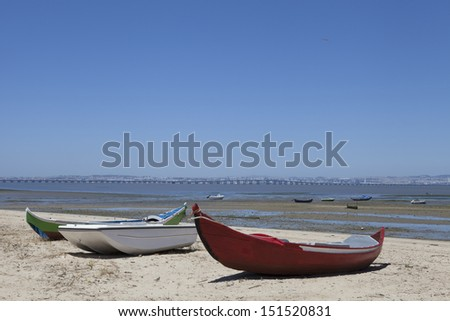 Fishing wooden boats on a sandy beach with light sun and bright sky. - stock photo