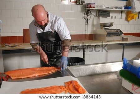 fishmonger cutting slices of smoked salmon fresh from the smoke house