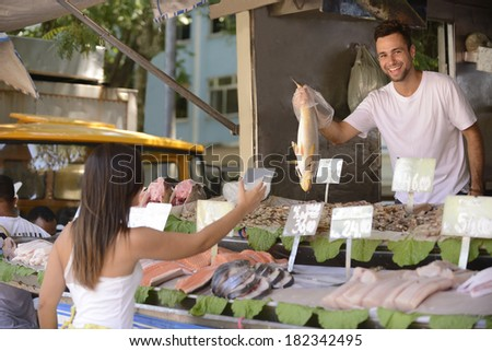 Fishmonger handing out a fish to a customer at an open retail fish market.