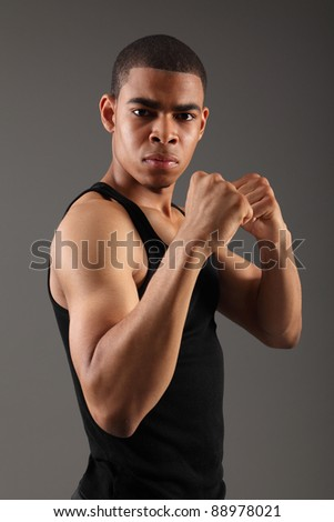Fist clenched and bicep muscles on fit body of a handsome young african american man, showing off his physique in an aggressive pose wearing black vest, shot against grey background. - stock photo