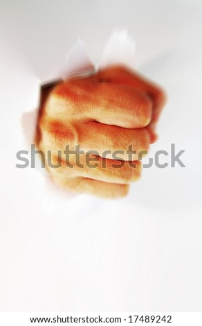 fist creating a hole punching thru a wall - stock photo