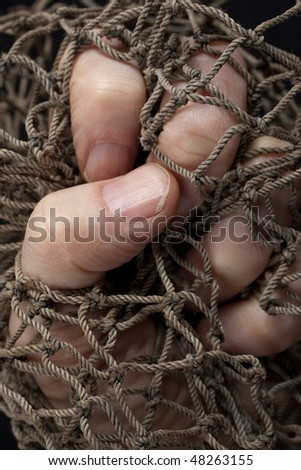 Fist ensnared in an old hemp fishing net. Selective focus. Horizontal or vertical. - stock photo