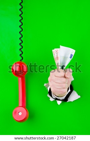 Fist holding Euros and a telephone receiver dangles nest to it. - stock photo