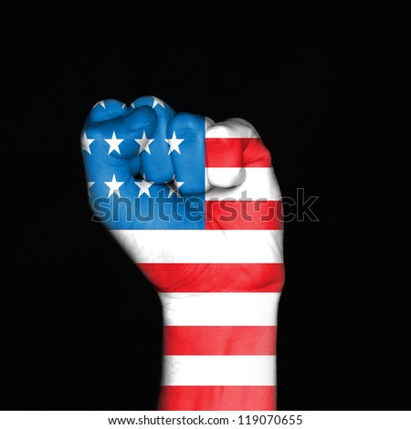 Fist painted in colors of american flag over dark background - stock photo