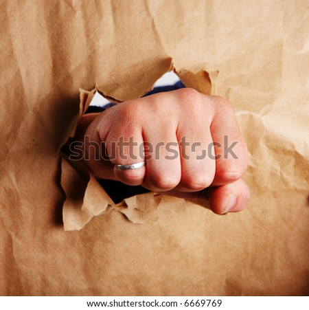 Fist punching paper creating a torn hole - stock photo