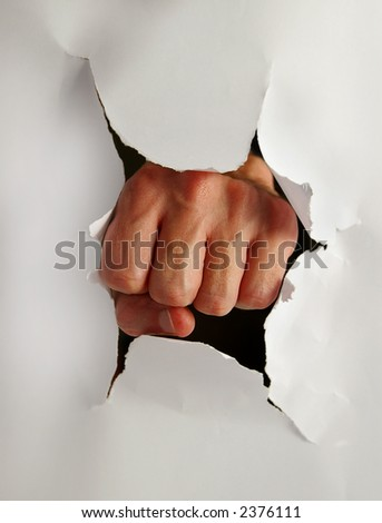 Fist punching thru paper creating a torn hole - stock photo