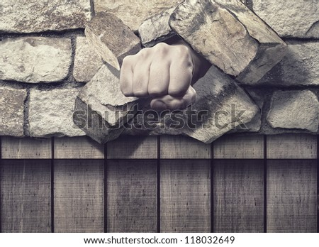 Fist through the Brick Wall - stock photo