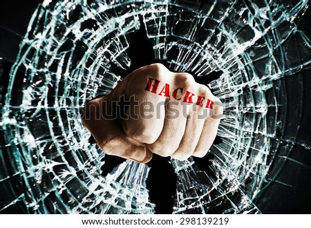 Fist with Hacker text punching thru a glass window  -- cyber crime concept                              - stock photo