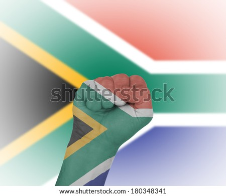 Fist wrapped in the flag of South Africa and flag in the background - stock photo