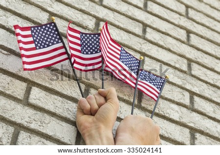 Fists clench small American flags in patriotic imagery