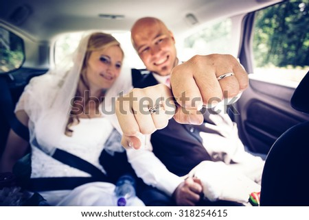 Fists of bride and groom with a new wedding rings. The newlyweds are located inside of their car on back seats. Faces with expressions of happiness in the background. (Focused on fists of newlyweds) - stock photo