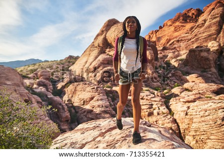 fit african american woman hiker walking on cliff edge at red rock canyon