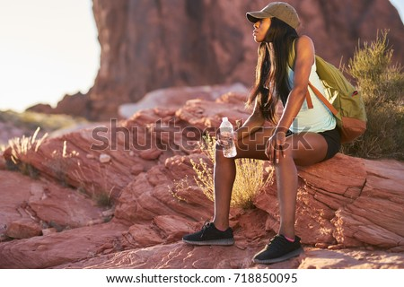 fit african american woman resting with water bottle during hike at valley of fire park