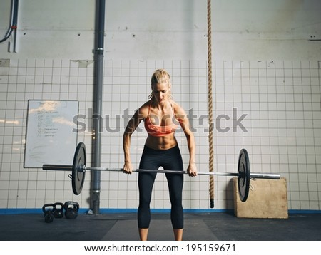 Fit and attractive caucasian female holding a barbell in her hands. Crossfit woman lifting heavy weights in gym. - stock photo