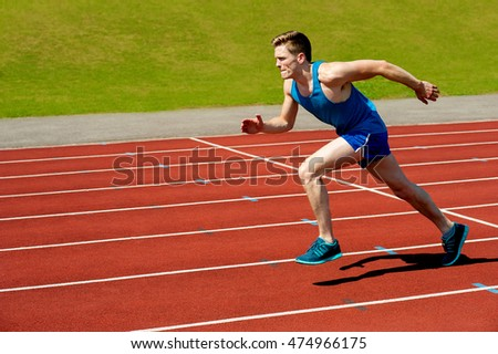 Fit and confident man running in red race track.