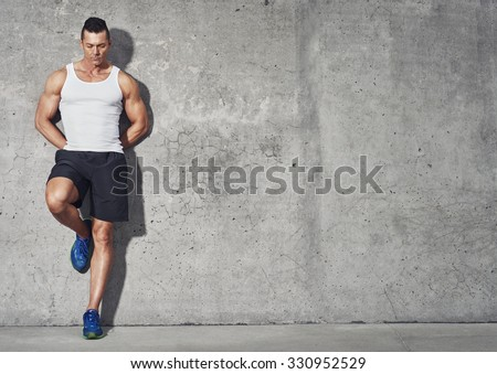 Fit and healthy man, muscular build portrait, fitness concept with copy space on grey background - stock photo