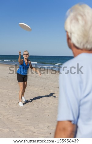 Fit and healthy senior man woman couple playing on a deserted beach by the sea - stock photo