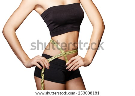 Fit and healthy young lady measuring her waist with a tape measure in centimeters and millimeters. She has her black gym exercise outfit on. Isolated image on white. - stock photo