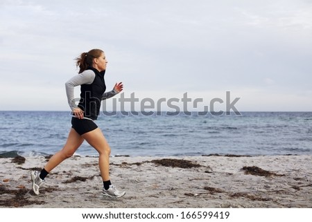 Fit and healthy young woman running along shoreline. Caucasian female athlete exercising running on beach. Beautiful young woman runner running on beach. - stock photo