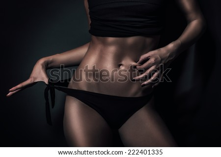 Fit and no fat young woman showing abs and thin skin around belly