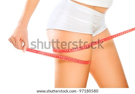 Fit and slim / Beautiful and fit young woman measuring her sexy body. Diet and body care concept. - stock photo