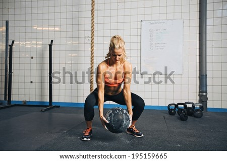 Fit and strong female athlete working out with a medicine ball to get better core strength and stability. Woman doing crossfit workout at gym. - stock photo
