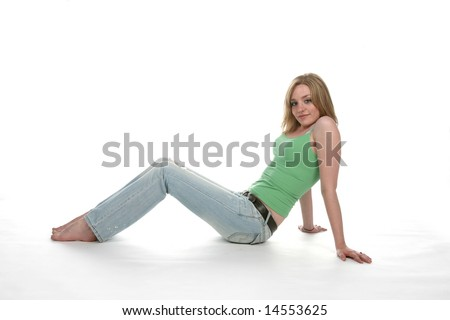 fit and toned teen sitting and leaning back on her arms - stock photo