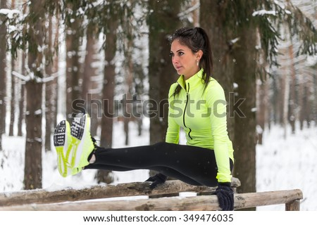 Fit athlete woman doing abs exercises street work out in woods winter park