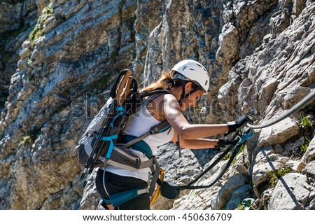Fit athletic woman mountaineering climbing a steep rocky cliff face with the aid of ropes on a sunny summer day - stock photo