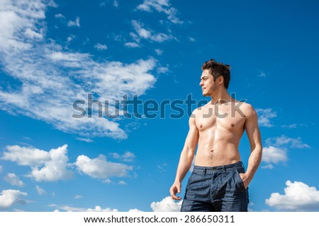 Fit athletic young man with bare torso enjoying sunny day under scenic blue cloudy sky. Concept of recreation, healthy lifestyle and well being