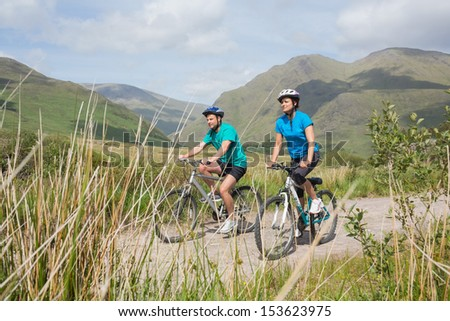 Fit attractive couple cycling together through majestic countryside - stock photo