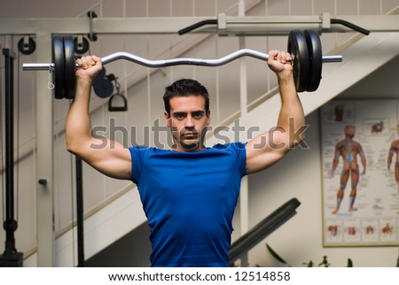 Fit, attractive man lifting a barbell over his head (overhead press) in a gym - stock photo